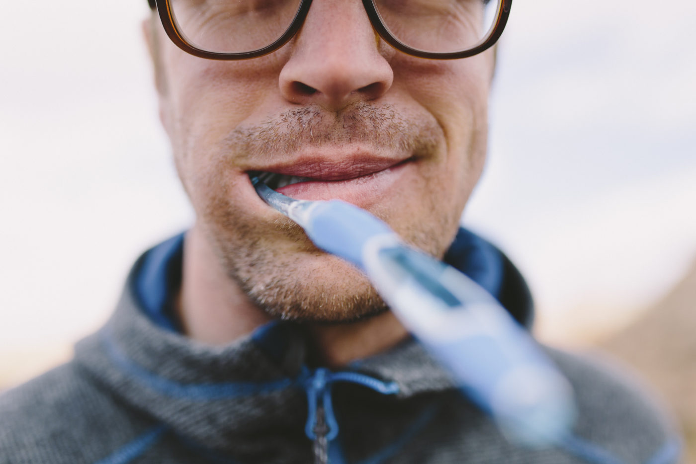 A man smiles with a toothbrush in his mouth